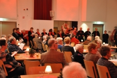 Het koor zingt tenslotte nog staande rondom in de zaal